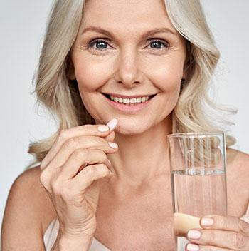 Older woman taking vitamin pill