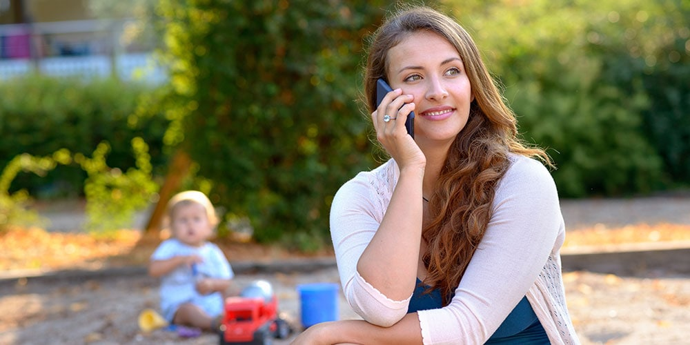 Woman on phone with baby playing in background