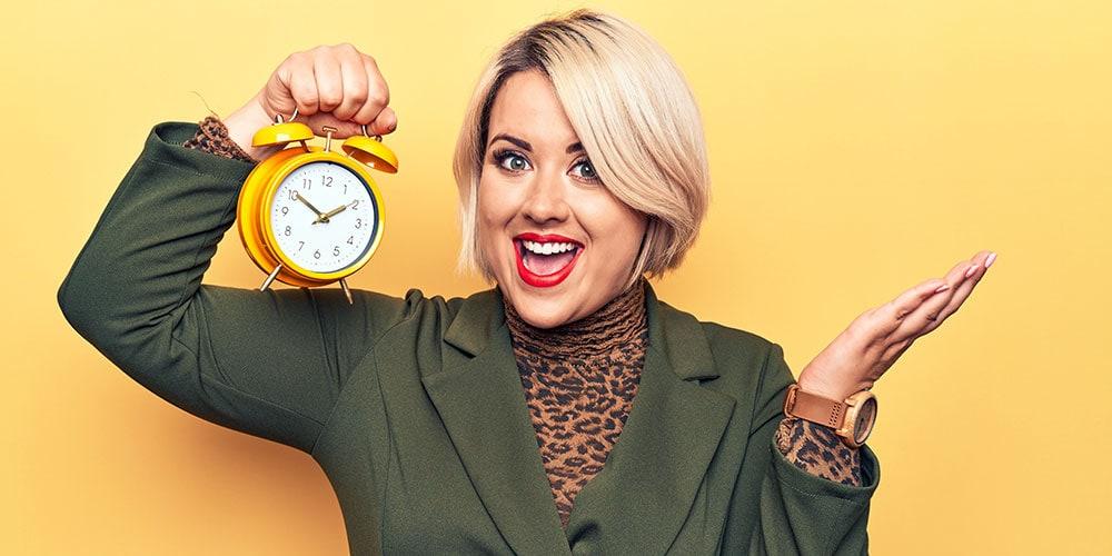 Smiling blonde woman holding clock