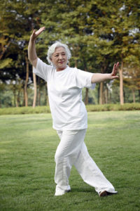 Older woman doing tai chi in the park