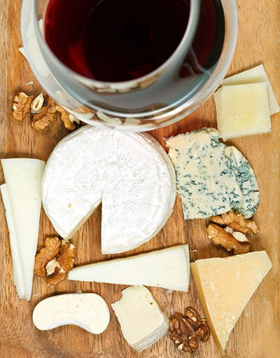 A glass of wine and assortment of soft cheeses